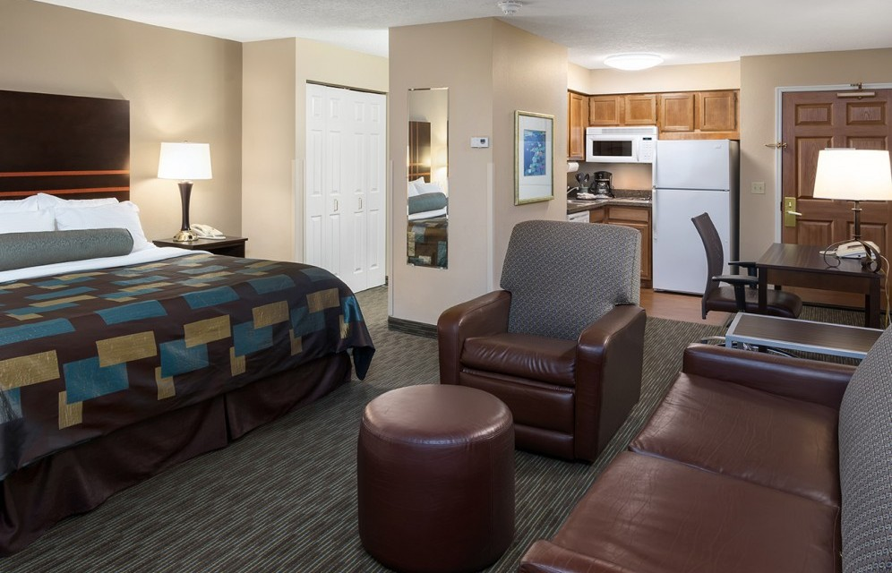 Spacious Suite with King bed, chair sofa, and view into the kitchen