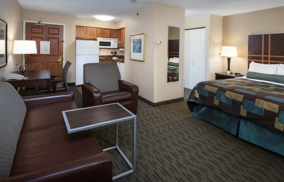 Suite with couch, chair, desk, and view into the kitchen